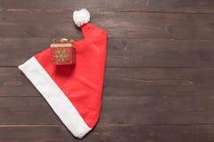Czerwony kapeluszu i prezenta pudełko jest na drewnianym tle z pustym zdrojem Obraz Stock