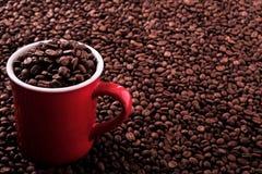 Czerwony kawowy kubek wypełniający z fasoli tła kopii przestrzenią Fotografia Stock
