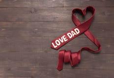 Czerwony kierowy krawat jest na drewnianym tle Fotografia Stock