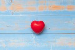 czerwony kierowy kształt na błękitnym pastelowego koloru drewnianym tle fotografia stock