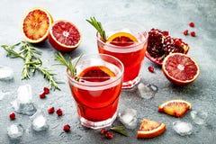 Czerwony koktajl z krwionośną pomarańcze i granatowem Odświeżający lato napój Wakacyjny aperitif dla przyjęcia gwiazdkowego Zdjęcia Royalty Free