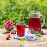 Czerwony kompot z wiśnią, truskawka, agrestowa nd malinka na drewnianym stole Obraz Royalty Free