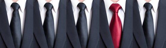 Czerwony krawat między czarnymi krawatami Zdjęcia Stock