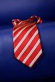 Czerwony krawat na błękitnej kanapie Zdjęcia Stock