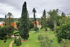 Czerwony książe pałac z wiele drzewami na przedpolu w kędziorka parku w Ostrov nad Ohri mieście przy zaczynać czeska jesień Zdjęcia Stock