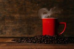 czerwony kubek z kontrparą na stosie świeże piec kawowe fasole nad drewnianym stołem Obrazy Stock