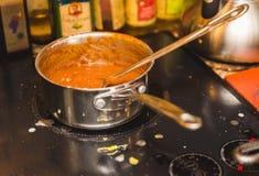 Czerwony kumberland w Stalowym garnku na szkło wierzchołka kuchence fotografia stock