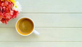 Czerwony kwiat na drewnianym stole i filiżanka kawy Obraz Stock
