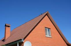 Czerwony metal Zadasza Nowego cegła dom Starego zatartego czerwonego metalu dachowa płytka i komin Zdjęcie Stock