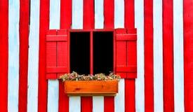 Czerwony okno na czerwonej i białej drewnianej ścianie zdjęcie stock