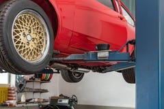 Czerwony Oldtimer samochód na dźwignięciu zdjęcia stock