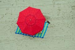 Czerwony parasol przy morze plażą Obraz Royalty Free