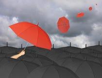 Czerwony parasol w ręce i Otaczający czarnym parasolem Obraz Stock