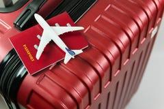 Czerwony paszport i samolot modelujemy na czerwonym bagażu zdjęcia stock