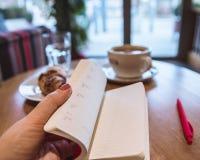 Czerwony pióro i jesteśmy na stole w kawiarni, filiżanka kawy i croissant na tle, Żeńska ręka trzyma a obrazy stock