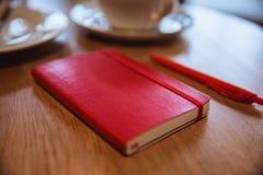 Czerwony pióro i jesteśmy na stole w kawiarni, filiżanka kawy i croissant na tle, fotografia royalty free
