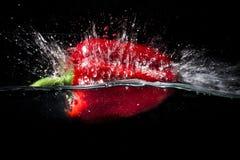 Czerwony pieprz spada wewnątrz woda Zdjęcie Stock