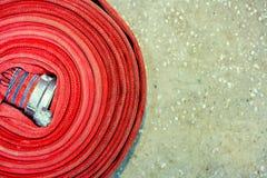 Czerwony pożarniczy wąż elastyczny przekręcał w spiralę Odgórny widok z kopii przestrzenią fotografia royalty free