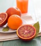 Czerwony pomarańczowy liścia i szkła soku pomarańczowego cytrus barwi makro- zakończenie w górę ranku śniadania zdjęcia stock