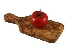 Czerwony pomidor na oliwnej drewnianej tnącej desce fotografia stock