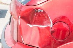 Czerwony porysowany samochód z uszkadzającą farbą w i wgniatającą szkodą metalu ciało od karambolu trzaska parking lub wypadku obrazy stock