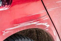 Czerwony porysowany samochód z uszkadzającą farbą w trzaska wypadku na ulicie lub parking w mieście zdjęcia stock