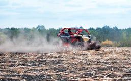 Czerwony powozik śpieszy się przez pola w pyle zdjęcia royalty free