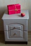 Czerwony prezent i jabłko na nightstand Zdjęcia Stock