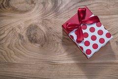 Czerwony prezent urodzinowy na drewnianej deski świętowań pojęciu Fotografia Stock