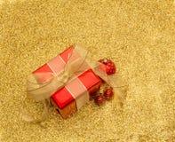 Czerwony prezenta pudełko i baubles z złocistym faborkiem na złocistej błyskotliwości z powrotem Obraz Stock