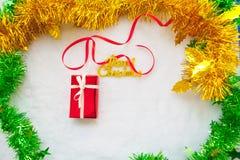 Czerwony prezenta pudełko i złocisty wesoło bożych narodzeń tekst z czerwonym faborkiem Fotografia Stock