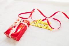 Czerwony prezenta pudełko i złocisty wesoło bożych narodzeń tekst z czerwonym faborkiem Obrazy Stock