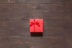 Czerwony prezenta pudełko jest na drewnianym tle z pustą przestrzenią Fotografia Royalty Free
