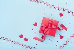 Czerwony prezenta pudełko, serpentyna, serca i confetti na błękitnego tła odgórnym widoku, dni karty pozdrowienia s walentynki Mi Zdjęcia Stock