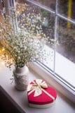 Czerwony prezenta pudełko w kształcie serce i bukiet piękna biała łyszczec blisko okno z raindrops w świetle dziennym Zdjęcia Stock