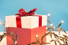 Czerwony prezenta pudełko z łękiem i bożonarodzeniowe światła na biurku obraz stock