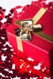 Czerwony prezenta pudełko z złotym łękiem i wiele czerwoni mali serca na bielu Fotografia Stock