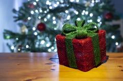 Czerwony prezenta pudełko z zaświecającą zieleni choinką z bożonarodzeniowe światła w tle i koronką zdjęcia stock