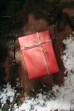Czerwony prezenta pudełko i futerka drzewo na drewnianym tle Obraz Royalty Free
