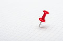 Czerwony pushpin na białym papierze Obrazy Stock