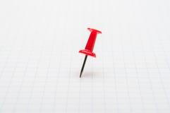 Czerwony pushpin na białym papierze Fotografia Royalty Free