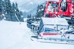 Czerwony ratrac snowcat przy pracą dalej na narciarskim skłonie zdjęcie royalty free