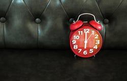 Czerwony retro budzik na ciemnej kanapie Fotografia Stock