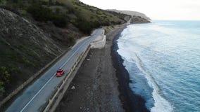 Czerwony retro samochodowy jeżdżenie blisko morza na drodze Filmowy widok z lotu ptaka zbiory