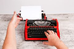 Czerwony rocznika maszyna do pisania maschine z białym pustego papieru prześcieradłem na stole fotografia royalty free