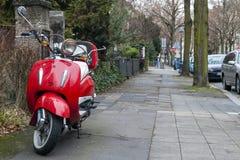 Czerwony rocznika motocykl parkujący na ulicznym chodniczku Zdjęcie Stock