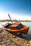 Czerwony rowboat lying on the beach przy brzeg Obraz Stock