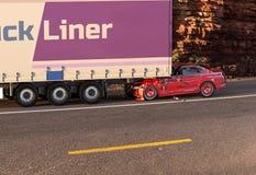 Czerwony samochód rozbijał na dużej ciężarówce Na drodze z środowiskiem zdjęcia royalty free