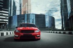 Czerwony samochodu pobyt na asfaltowej drodze w mieście przy dniem zdjęcie royalty free