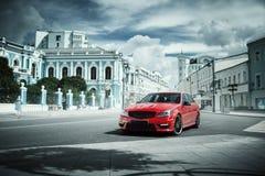 Czerwony samochodu pobyt na asfaltowej drodze w mieście przy dniem obrazy stock